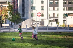 TRIBUNE PHOTO: JONATHAN HOUSE - Chapman School kindergarteners Emaline Porter, (left) Tess Groom (in pink), and Caroline Pittman play soccer in The Fields Park, across from a construction zone.