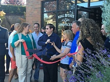 SUBMITTED PHOTO - Larry Micohn, owner of Windermere Happy Valley, broke out the big scissors last month as he cut the ribbon to Windermere's newest office location.