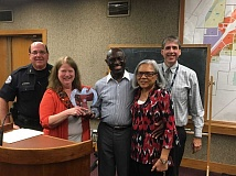 COURTESY PHOTO: CITY OF WOODBURN - Ewart Brown (center) and his wife, Linda, were honored at the Sept. 25 Woodburn City Council meeting. He is congratulated by Police Chief Jim Ferraris (left), Mayor Kathy Figley (holding the plaque) and City Administrator  Scott Derickson (right).