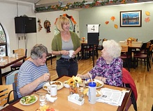 PMG PHOTO: BARBARA SHERMAN - Tigard Senior Center director Vicki Adams chats with a couple of ladies enjoying lunch.