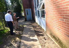REVIEW FILE PHOTO: VERN UYETAKE - Randy Miller, the districts executive director of project management, and Lake Grove Elementary School Principal Carol Whitten look at some of the maintenance issues at Lake Grove, including exterior masonry problems. Lake Grove is slated for replacement in Phase 3 of the school bond, which the district intends to put before voters in 2025.