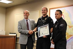 TIDINGS PHOTO: PATRICK MALEE - Officer Sam Tooze was presented with the award alongside Mayor Russ Axelrod, left, and Police Chief Terry Timeus.