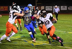 PAMPLIN MEDIA: LON AUSTIN - Gladstone's Dylan Farris (33) finds running room as teammate Quinn Carl (46) blocks Crook County's Zachary Rictor during Thursday's Tri-Valley Conference football game in Prineville.