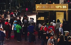 PAMPLIN MEDIA GROUP PHOTO - Portlanders line up Saturday for their free baloney sandwiches from the temporary Donald Trump BS food cart in Pioneer Square.
