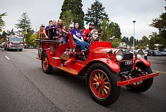 ADAM WICKHAM/FOR THE REVIEW - Associated Student Body officers hitch a ride on The Jimmy during Lake Oswego High School's homecoming parade last month. Seated in the front seat of the vintage 1923 fire engine with 12th-grader Cher Feng is firefighter Troy Waddell.