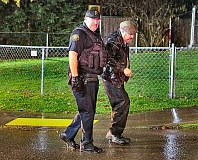 DAVID F. ASHTON - In a downpour, a Portland Police officer escorts the arrested driver toward a patrol car.