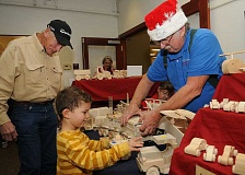 TIDINGS PHOTO: VERN UYETAKE - It was the eighth time around for the annual Holiday Bazaar at the West Linn Adult Community Center Nov. 12.  Woodworker John Basquez shows Joe Beyer and his son Skyler his handcrafted toys.
