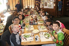 SUSAN MATHENY/MADRAS PIONEER - Students in Katie Lapke's class at Madras Elementary practice using napkins, passing food, and saying please and thank you at the dinner table at Black Bear Diner.