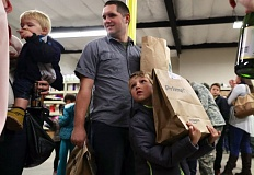 TIMES PHOTO: JAIME VALDEZ - Keith Maine and his son Peter, 7, came to Tigard on Wednesday morning and were surprised with supplies for Thanksgiving dinner from Amazon Prime Now.