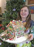NEWS-TIMES PHOTO - Forest Grove girl Daphne brought her gingerbread house entry to the News-Times office on Pacific Avenue for judging.