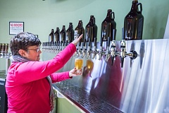TIMES PHOTO: JONATHAN HOUSE - Jo Renee Hartman, co-owner of Hops on Tap, pours a beer for a customer.