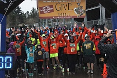 COURTESY OF CINDY AGGSON - Runners and walkers pose for a photo (in a downpour) during this year's annual Give n' Gobble held on Thanksgiving Day.
