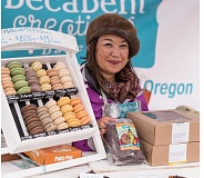 CHASE ALLGOOD - Vanessa Bunkler of Decadent Creations show off the bakerys treats at the Beaverton Fall Market. The bakery is opening soon in downtown Hillsboro.