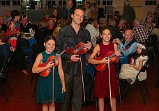 DAVID F. ASHTON - Ready to perform at the Southeast Portland Rotary Clubs Holiday Celebration at Oaks Park: Twins Sarah and Sophia Fisher, flanking their mentor, concert rock violinist Aaron Meyer.
