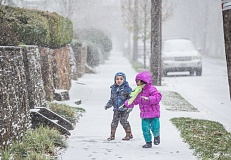 TRIBUNE PHOTO: JONATHAN HOUSE - Andre and Elisa Cabrera enjoy Thursday's snowstorm in Sellwood.