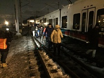 COURTESY PHOTO: KOIN 6 NEWS - A steady stream of cold passengers walked from the blocked MAX train to the Gateway Transit Center Friday night after being trapped by a downed high-voltage line on the train tracks.