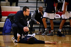 TRIBUNE PHOTO: JONATHAN HOUSE - Lake Oswego High athletic trainer Ron Moore helps a boys basketball player get loose before the Lakers' season opener last week against Jefferson