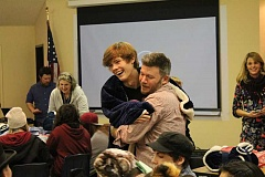SPOKESMAN PHOTO: ANDREW KILSTROM - Junior Alec Tompkins, left, gives teacher Ben Whitcomb a big hug after receiving a blanket Tuesday, Dec. 13.