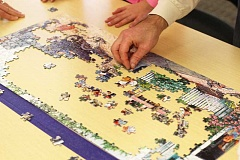 SUBMITTED PHOTO  - Participants piece together a jigsaw puzzle at a prior Sherwood Jigsaw Puzzle Competition, which is set for Feb. 18 at the Sherwood Police Department Community Room.