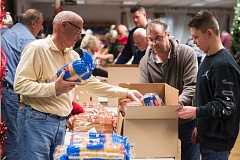 FILE PHOTO - Gresham Elks Club members pack food boxes for National Guard members and others in the community during a recent holiday boxing event.