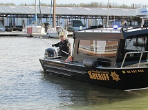 SPOTLIGHT PHOTO: COURTNEY VAUGHN - A Columbia County Sheriff's Office deputy on a marine unit boat skims the Scappoose Bay for signs of a sunken vehicle Wednesday afternoon. The Sheriff's Office and other emergency response agencies were at the scene where a woman drove her vehicle into the bay.