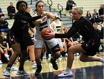 DAN BROOD - Tigard senior post Natalie Clark (center) battles a pair of Oregon City players for the ball during play at the Nike Interstate Shootout.