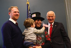 OUTLOOK PHOTO - Secretary of State Dennis Richardson mugs for the camera with Stephanie Martin-Seawall, an American citizen born in France, and her husband. She did not arrive at the ceremony wearing the hat.