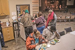 NEWS-TIMES PHOTO: CHASE ALLGOOD - Volunteers at an overnight shelter in the Sonrise Forest Grove church serve dinner as part of their warming shelter Thursday as grateful guests pray before the meal.