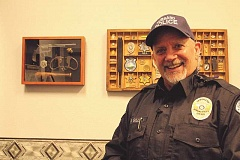 LINDSAY KEEFER - Hubbard's Interim Police Chief Bill Gill stands in his office next to framed pieces of police memorabilia he has collected over his 24 years in the police force. Gill announced he will retire at the end of February.