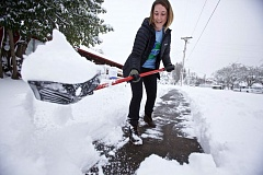 TIMES PHOTO: JAIME VALDEZ - It's going to take a while for the region to dig out from the biggest snowfall since 2008, but that didn't stop Amber Layton from getting started. The lead outreach worker with HomePlate Youth Services, and a Philadelphia native no stranger to snowstorms, she shoveled snow on a sidewalk in front of the organization's office in Beaverton Wednesday morning.
