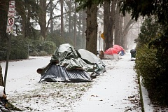 OREGON PUBLIC BROADCASTING - Tents gather snow during a winter storm on Saturday, Jan. 7, 2017. Of five occupants interviewed, none knew the location of warming shelters, and only one expressed interest in going.