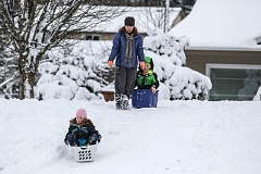 TRIBUNE PHOTO: JON HOUSE - Improvised sleds work just as well for these Southeast Portland kids marooned by unusual snowfall.