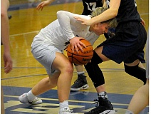 SETH GORDON - Newberg point guard Taylor Rarick ducks under Canby wing Mackenzie Lee during the Tigers' 70-56 home win Friday night. Rarick scored 39 points.