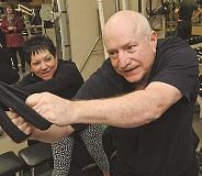 TIDINGS PHOTO: VERN UYETAKE - Robin Mennis does a trunk rotation exercise with trainer Louise Gillis.