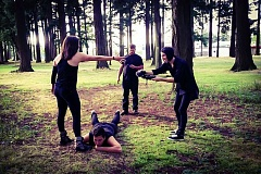 CONTRIBUTED PHOTO - Claire Palmiter reaches for the camera, operated by Skyler O'Roke, during a fight scene on the set of 'Variance: Aconite.' Sky's brother, Kamrin, lies on the ground. Anton Bocharov, the film's main villain, stands between camera operator and actor.