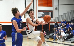 SPOTLIGHT PHOTO:JAKE MCNEAL - Scappoose junior guard Jerad Toman goes in for a layup against Valley Catholic junior post Jack Grasberger during the Valiants' 79-48 win at Scappoose High School on Friday.