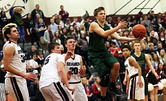 DAN BROOD - Tigard senior guard Luke Smith goes airborn as he dishes off a pass in Friday's game at Sherwood.