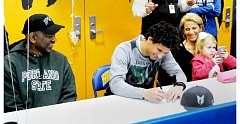 SETH GORDON - NHS senior Anthony Adams fills out the paperwork to play football at Portland State University during a signing ceremony Feb. 1.