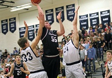 PMG PHOTO: MILES VANCE - Sherwood's Jace Sucher puts up a shot between Lake Oswego's Brooks Boutwell (left) and Sterling Roberts during Lake Oswego's 59-45 win at Lake Oswego High School on Friday.
