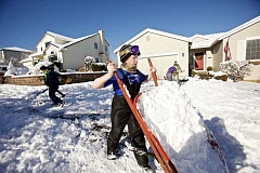 FILE PHOTO - Aidan Kelly, 11, dumps snow from a wheelbarrow in 2017.