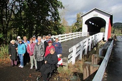 COURTESY OF JUANITA POHL CENTER - A group of seniors on a Juanita Pohl Center all-day tour of some of Oregon's covered bridges poses for a photo in a picturesque spot.