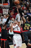 TRIBUNE PHOTO: JOSH KULLA - Kent Bazemore (right) of Atlanta gets a hand on a close-range shot by Trail Blazers guard CJ McCollum.