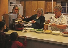 INDEPENDENT PHOTO: JULIA COMNES - (From left) Kristi Stokley, Chris Hindman and Lavon Rockford serve baked potatoes and toppings at Immanuel Lutheran's Feb. 8 dinner.