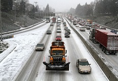 PAMPLIN MEDIA GROUP: JONATHAN HOUSE - A snow plow slowly moves northbound in the snow during heavy traffic in North Portland.