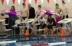 PMG PHOTO: MILES VANCE - Newberg's Tina Childress (right) launches herself off the blocks at the beginning of her win in the 50-yard freestyle during the Three Rivers League district meet at Mt. Hood Community College Aquatic Center on Feb. 11.