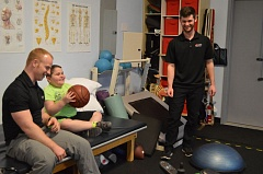 SPOTLIGHT PHOTO: COURTNEY VAUGHN - Joey Bates (middle) grips a basketball during physical therapy exercises in January. The Scappoose boy was diagnosed with Duchenne muscular dystrophy at the age of 4.