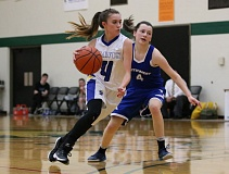 REVIEW/NEWS PHOTO: JIM BESEDA - North Clackamas Christian's Jenna Lay (left) drives around Southwest Christian's Maddie Lang during Thursday's Valley 10 League tournament game at Multnomah University.