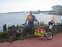 SUBMITTED PHOTO - Oregon City resident Bill Upton celebrates the completion of his 2010 bike ride across the country, ending here in Portland, Maine.