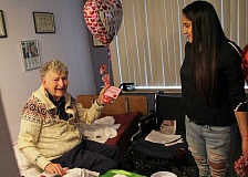 INDEPENDENT PHOTO: JULIA COMNES - Danyela Lopez surprises French Prairie resident Ed J. with candy and a balloon.