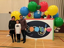 COURTESY: GOOGLE - Sixth-grader Michael Lei and his parents stand Thursday with a giant version of his artwork in the West Sylvan Middle School gym.